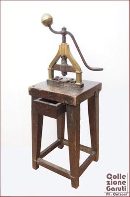 Bilanciere. Utilizzato per stampare o tranciare piccoli oggetti, datato alla fine del XVIII secolo e prodotto in Italia, del quale si conserva anche la base originale in noce.