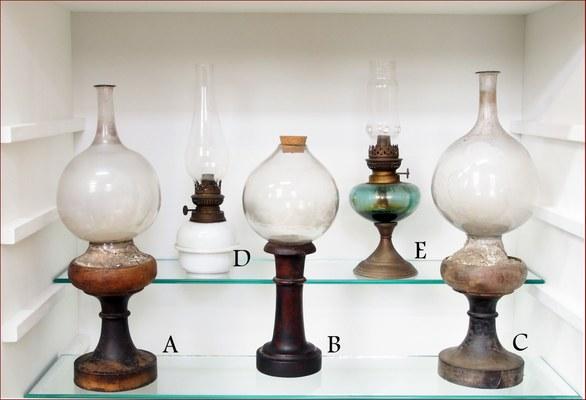 Bolle e lumi a petrolio. Bolle artigianali (A, B, C) e lumi a petrolio (D, E). Le bolle erano impiegate per concentrare la luce sull'oggetto in lavorazione e sono datate alla seconda metà del XIX secolo.